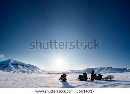 Three snowmobiles on a beautiful winter landscape