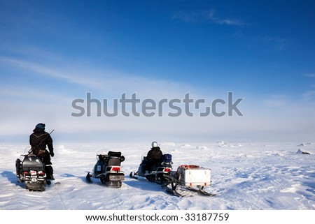 Three snowmobiles on a svalbard landscape of barren snow
