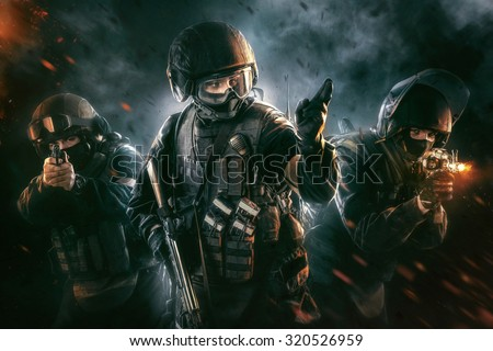 Three soldiers in full uniform with guns is going to attack. Uniform conforms to special services FSB (soldiers) of the Russian Federation. Shot in studio. Explosion on a black background