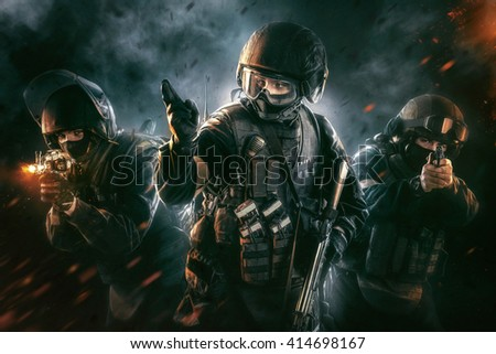 Three soldiers in full uniform with weapons is going to attack. Uniform conforms to special services FSB (soldiers) of the Russian Federation. Shot in studio. Explosion on a black background