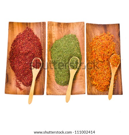 three spices . fennel, saffron, sumac  in powders with a wooden spoon. on a wooden stand in a row - isolated on white background