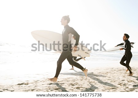 Three sport surfer friends running together towards the sea on a white sand beach carrying their surfing boards during a sunny golden day on vacation.