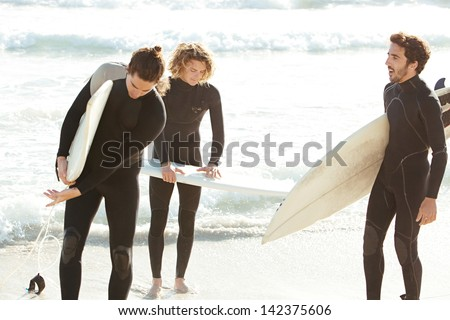 Three sport surfer friends standing together on a white sand beach carrying their surfing boards near the shore during a sunny golden day on vacation, getting ready for a surf session.