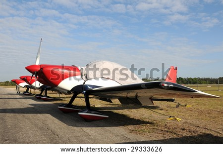 Three sports airplanes parked in a row