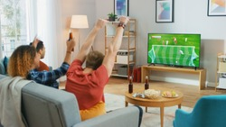 Three Sports Fans Sitting on a Couch in the Living Room Watch Important Soccer Match on TV, Cheering For their Team, Celebrates Doing YES Gesture after the GOAL Brings Victory to His Team.