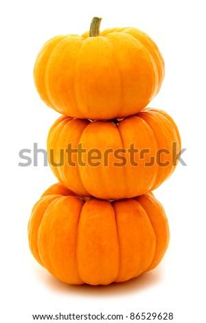 Three stacked mini pumpkins over white