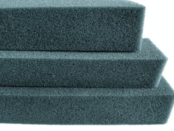 three stacked sheets of bluish spongy foam isolated on a white background