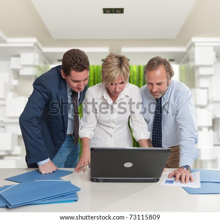 Three standing business people looking at a laptop screen in a modern interior