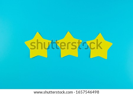 three star yellow paper note on blue background with copy space for text. Customer reviews, feedback, rating, ranking and service concept.