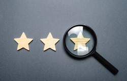 Three stars and a magnifying glass on a gray background. Authentication of the third star, rating fraud. Rating and status of the restaurant or hotel. Prestige.. High quality and reliability