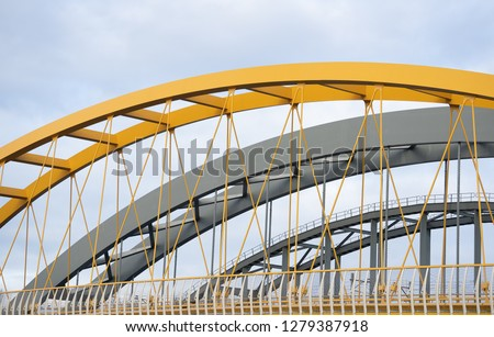 Three steel arch bridges lie side by side and span a river. One of the bridges is strikingly yellow in color and is the only suspension bridge. The other bridges are more traditionally constructed. #1279387918