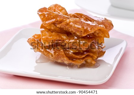 Three sticky butterfly cookies on a small plate on a pink napkin.