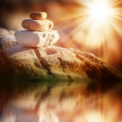 three stones stand on a balance beam, lighted bright sun. Reflection in water