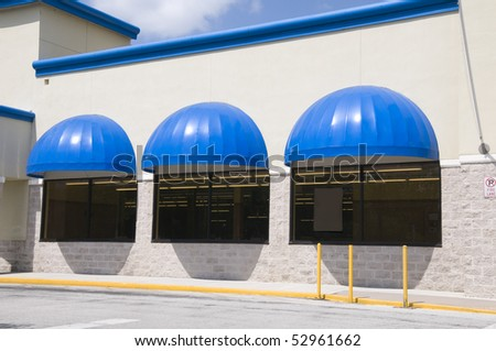 Three store front windows with blue curved canopy covers