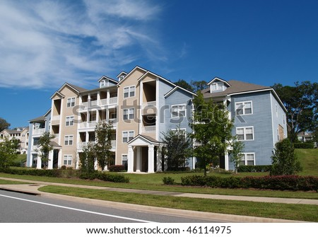 Three story condos, apartments or town homes with vinyl siding of blue and tan.