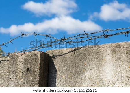 Three strands of barbed wire close-up, lying loosely on a fence of old concrete slabs with cracks and fungus against a blue sky and white clouds