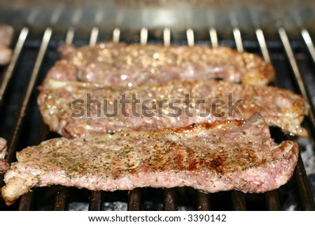 Three strip steaks cooking on the grill