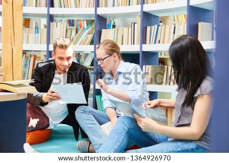Three students in a study group study together in the university library