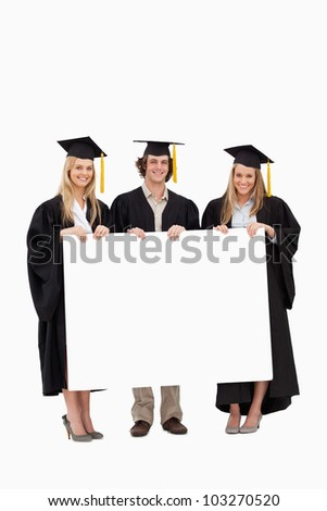 Three students in graduate robe holding a blank sign against white background