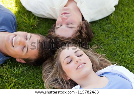 Three students resting together in the grass