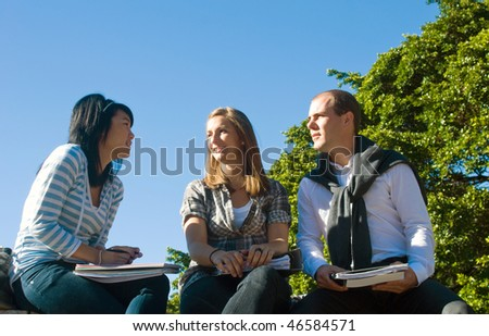 Three students talking casually in a university park on a beautiful sunny day - stock photo