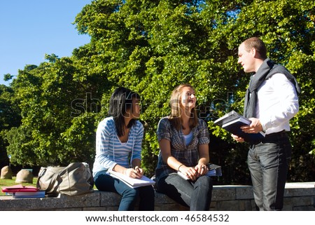 Three students talking on a small wall in a university park on a beautiful sunny day