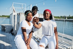 Three stylish african american friends, wear on white clothes at pier on beach making selfie. Street fashion of young black people. Black man with two african girls.