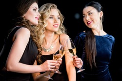 Three stylish young women in fashionable dresses drinking champagne together