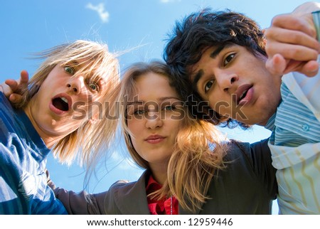 Three surprised friends embrace over sky background