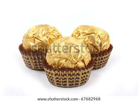 Three sweet chocolate bonbons in golden foil on white background