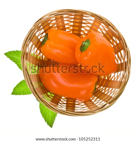 three sweet orange peppers in a wicker basket are a top view isolated on white background