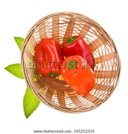 three sweet red peppers in a wicker basket are a top view isolated on white background
