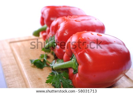 Three sweet red peppers on the kitchen table.