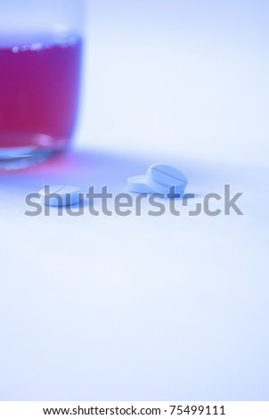 three tablets against the glass with liquid, white background, creative