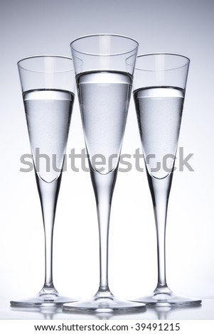 Three tall glasses filled with clear liquid