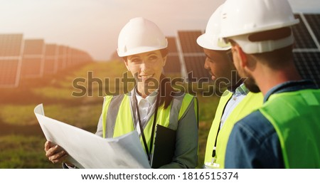 Three technical engineers review plan on paper and discuss. Two men listen to woman's explanations about nuances of work. Photo stock ©