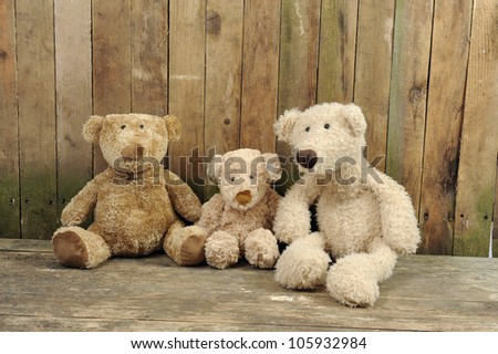 three teddy bears seated against a old wooden wall