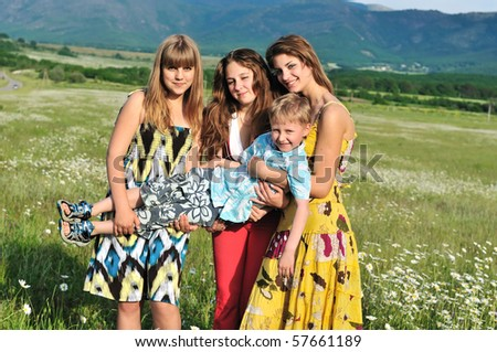 three teen girls holding one little boy in the daisy field