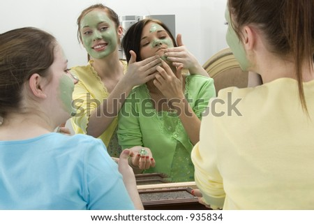 Three teen girls in bedroom mirror putting on facial mask.  Focus on reflection of girl in yellow.