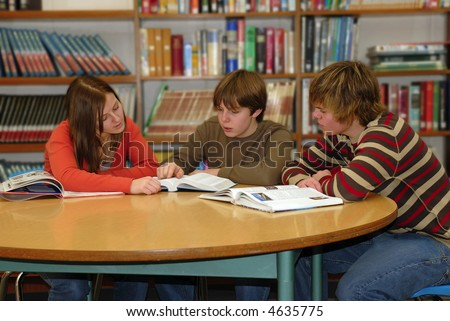 Three teen high school students work together studying in school library.