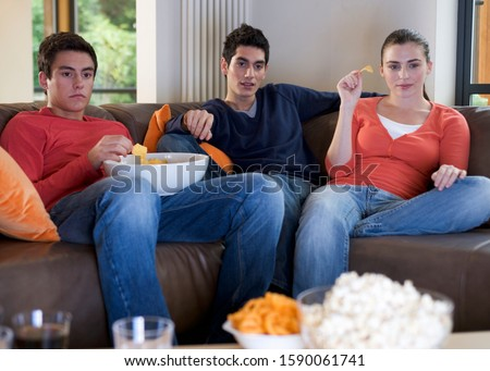 Three teenage friends watching television