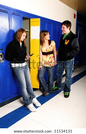 Three teenage students hang out in high school hallway