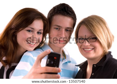 Three teenagers isolated. Boy on the middle is holding mobile phone and making the picture to the group.