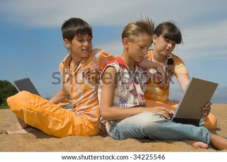 Three teens  with laptops on sea sand - stock photo