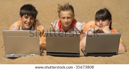 Three teens  with laptops on sea sand