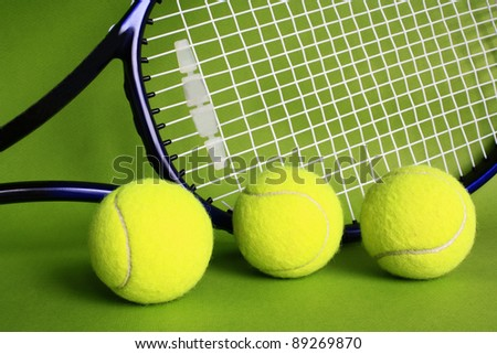 Three tennis balls and racket on green background.