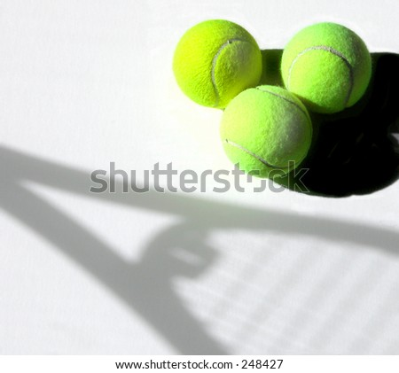Three tennis balls next to a shadow of a tennis racquet