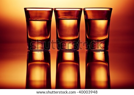 three tequila drinks with reflections in red light