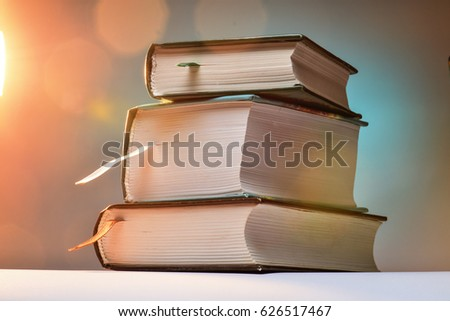 Three thick books on an abstract background with blurred lights. ストックフォト ©