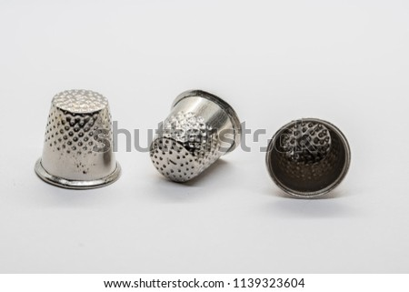 Three thimbles, used for sewing and needles, isolated on white background. - Shutterstock ID 1139323604